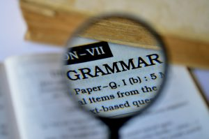 Grammar dictionary with magnifying glass to teach article usage